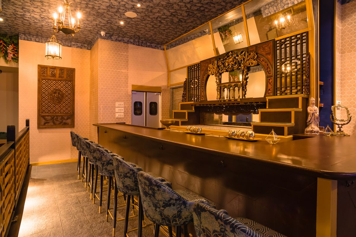 The bar area of the restaurant Wau with blue floral upholstered chairs facing an intricately carved bar area