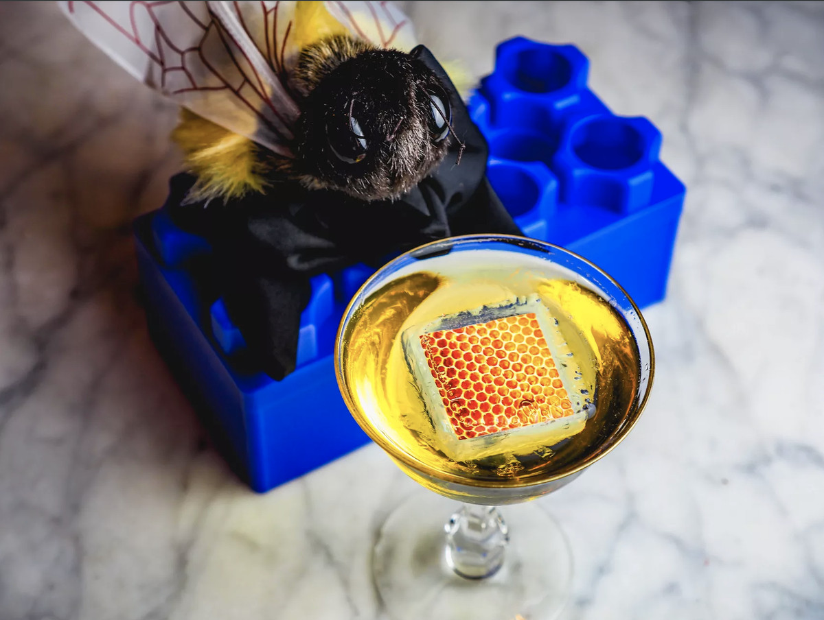 A martini glass filled with a yellow drink and honeycomb beside a large stuffed bee.