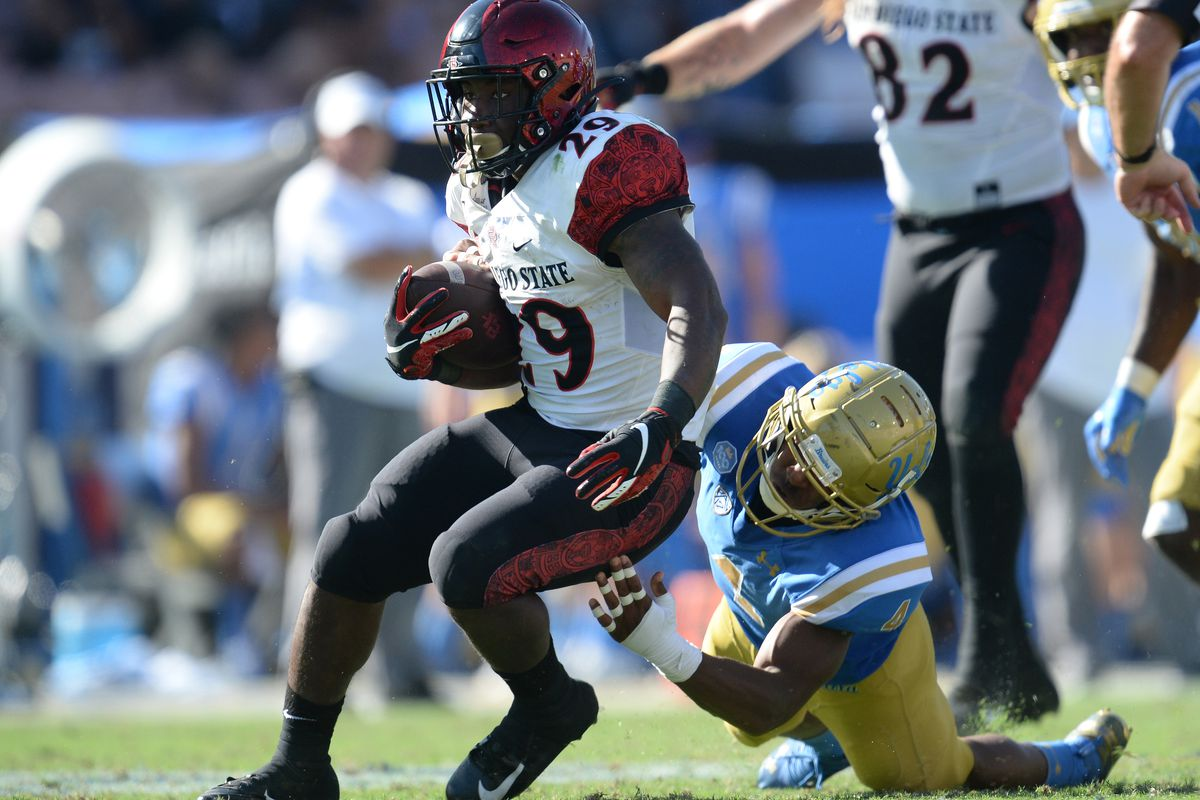 San Diego State running back Juwan Washington runs the ball ahead of UCLA defensive back Stephan Blaylock during the second half at the Rose Bowl.