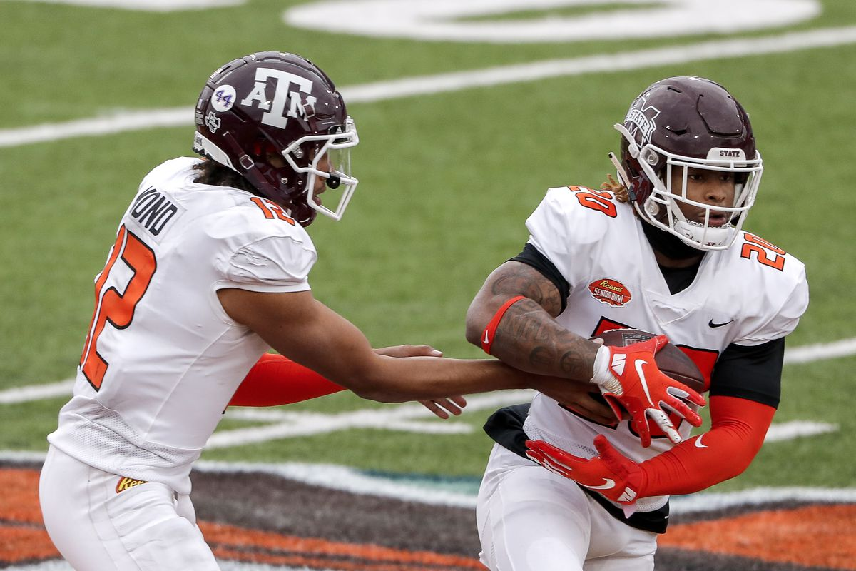 Quarterback Kellen Mond #12 from Texas A&M hands off the ball to Runningback Kylin Hill #20 from Mississippi of the American Team during the 2021 Resse's Senior Bowl at Hancock Whitney Stadium on the campus of the University of South Alabama on January 30, 2021 in Mobile, Alabama. The National Team defeated the American Team 27-24.