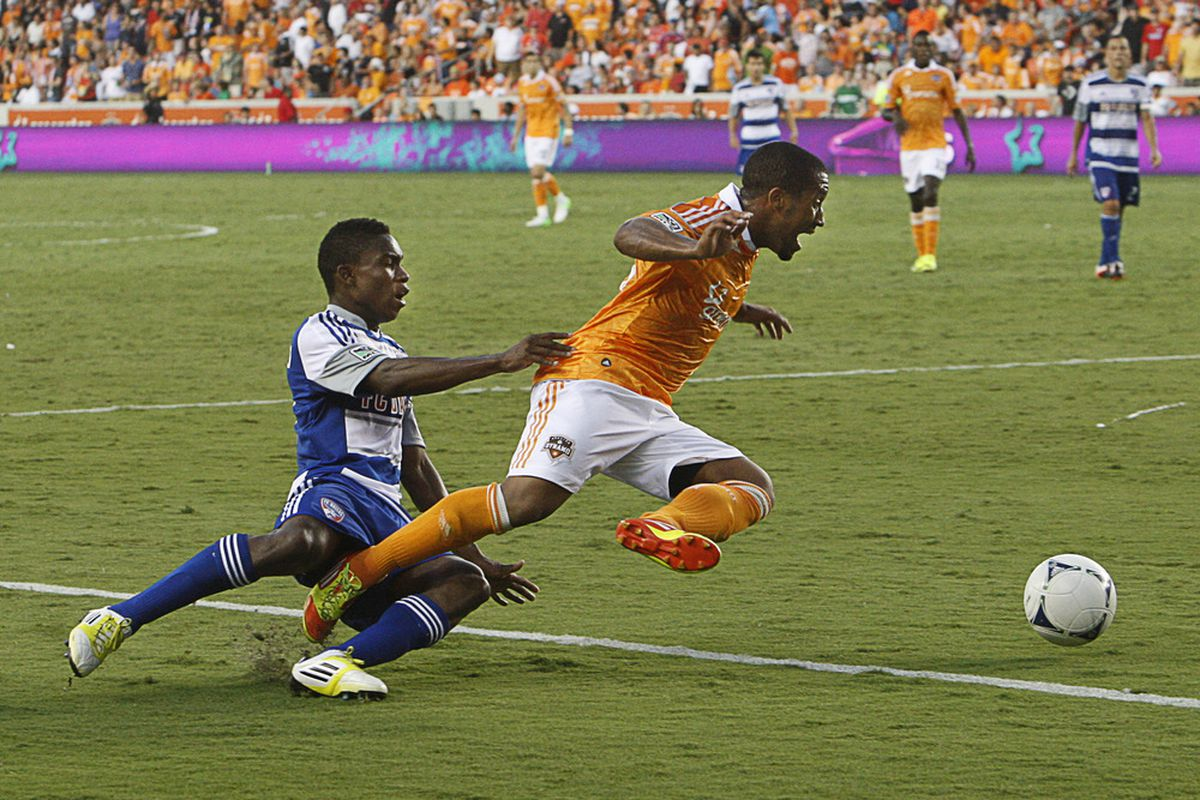 HOUSTON, TX - JUNE 16: Corey Ashe #26 of the Houston Dynamo is taken down by Fabian Castillo #7 of the FC Dallas at BBVA Compass Stadium on June 16, 2012 in Houston, Texas. Houston defeated Dallas 2-1.  (Photo by Bob Levey/Getty Images)