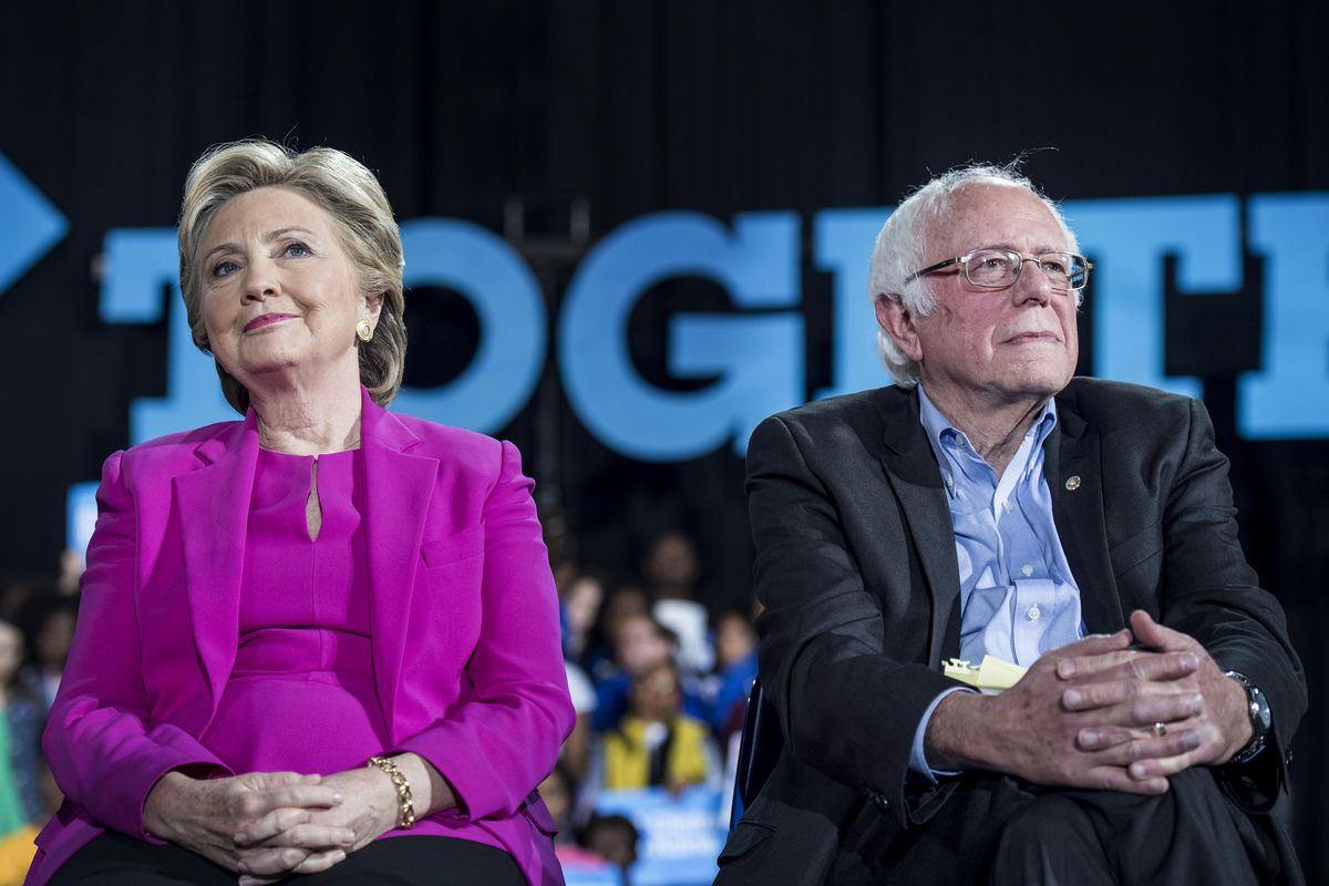 Hillary Clinton and Bernie Sanders sit next to one another on a stage.