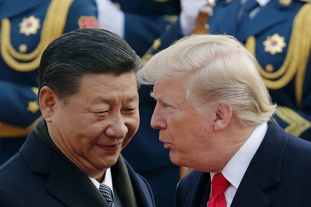 FILE - In this Nov. 9, 2017, file photo, U.S. President Donald Trump, right, chats with Chinese President Xi Jinping during a welcome ceremony at the Great Hall of the People in Beijing. China said Friday, Oct. 12, 2018 it is in contact with the United St