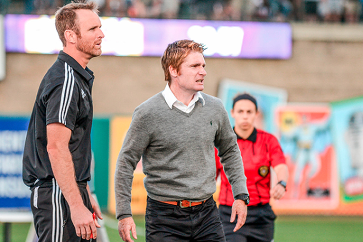 Louisville City Head Coach James O'Connor and his assistant Daniel Byrd look upset at play on the field.