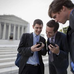 After delivering coffee to visitors to waiting to enter the Supreme Court, SCOTUS Blog interns check their smartphones for updates on the latest news as outside the court in Washington, Wednesday, June 26, 2013, as the justices are expected to hand down major rulings on two gay marriage cases that could impact same-sex couples across the country. From left to right are Dan Stein, Max Mallory, and Andrew Hamm.