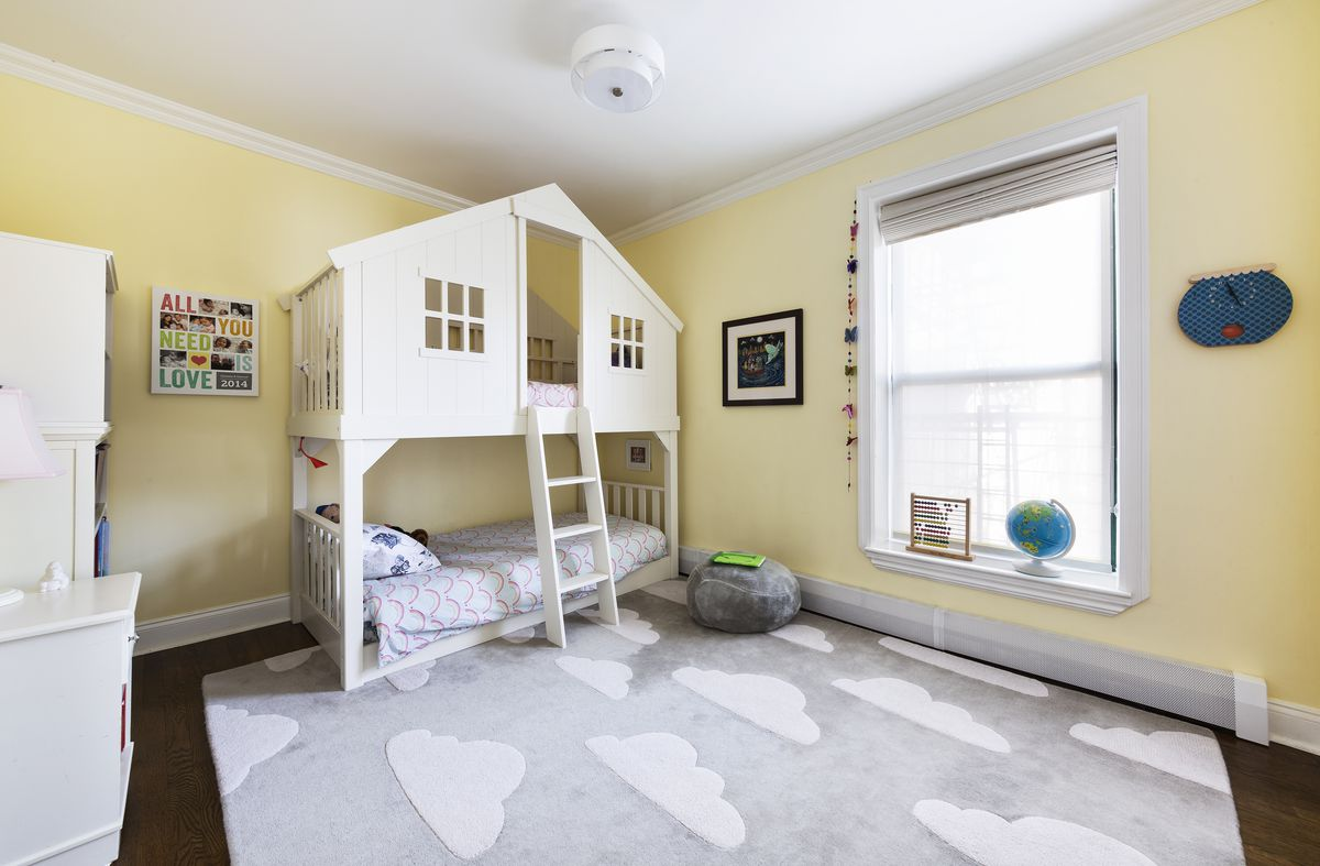 A kid's bedroom with light yellow walls, a light grey rug, and a bunk bed shaped as a tree house.