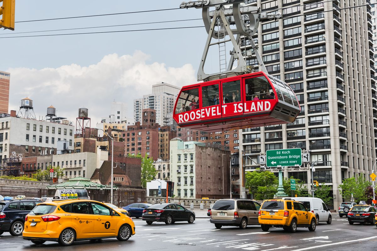The exterior of the Roosevelt Island Tram in New York City. The tram is red and is traveling on a cable above a city street with taxi cabs and cars.