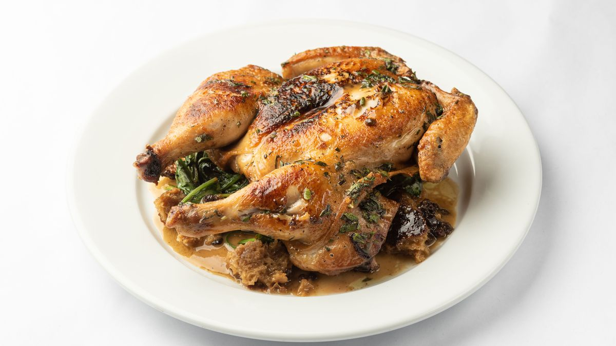 An angled photo on a white background of a plate with a full roasted chicken atop.