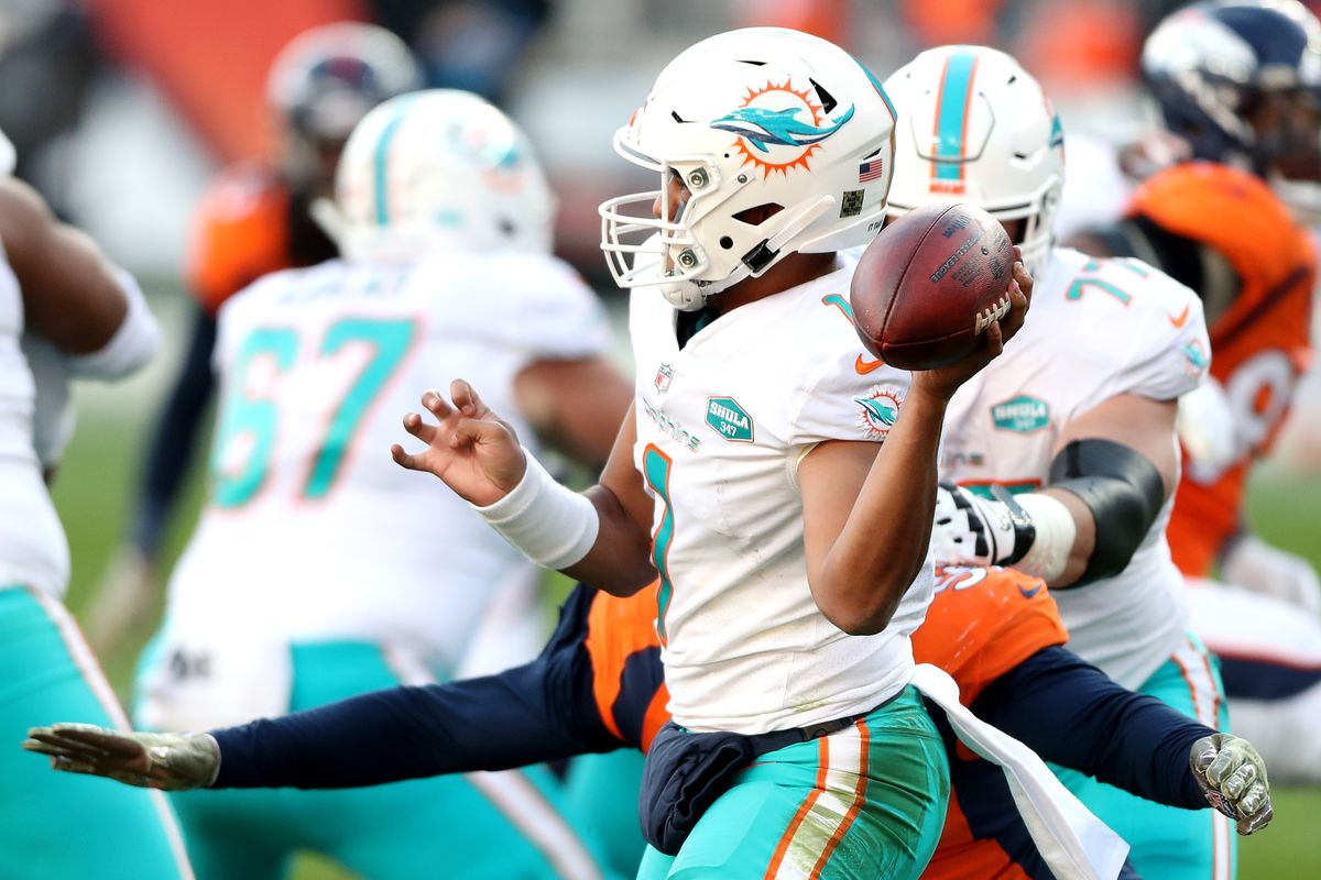 Tua Tagovailoa #1 of the Miami Dolphins passes under pressure during the second quarter against the Denver Broncos at Empower Field At Mile High on November 22, 2020 in Denver, Colorado.