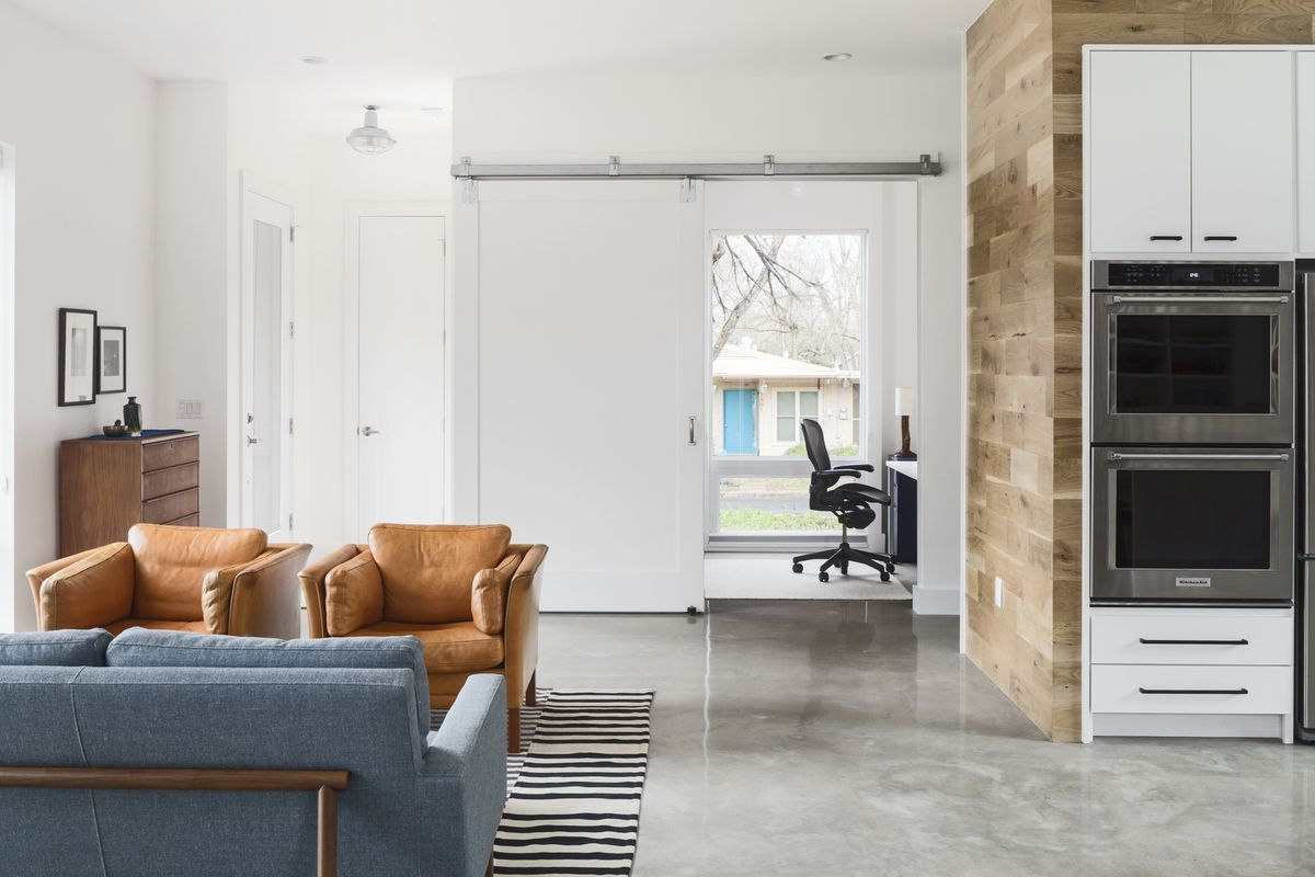 The living room opens up to the kitchen, and behnd is is an office with a sliding barn door.