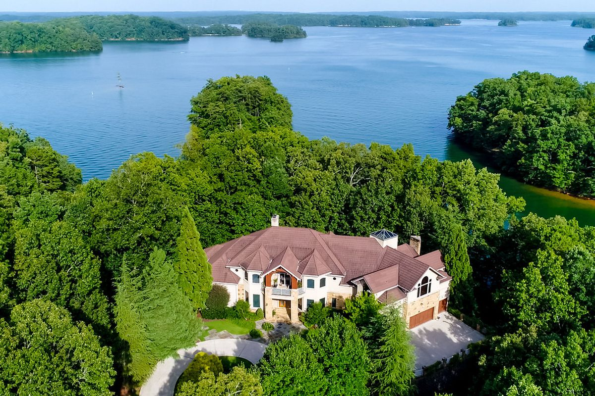 An aerial photo of a large house on a huge lake.