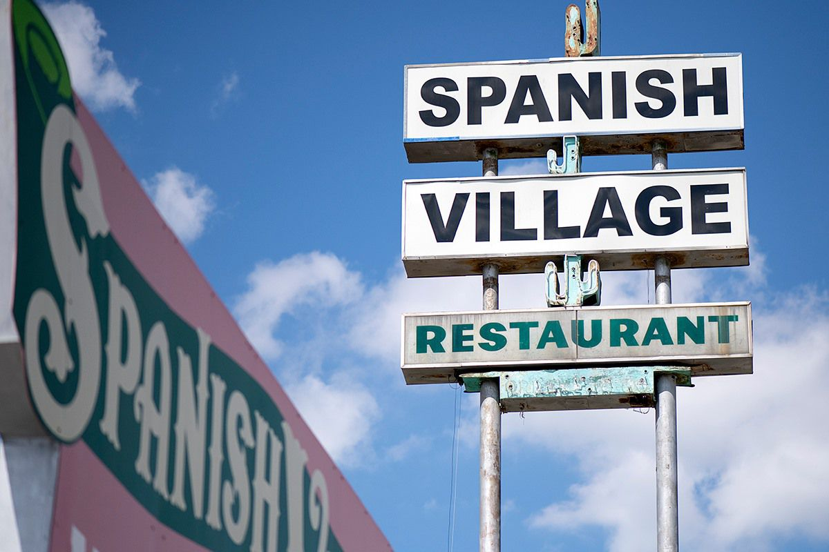 A restaurant sign shaped like a cactus which reads 'Spanish Village'