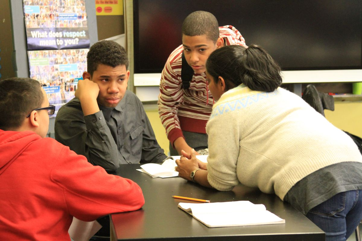 Bernie Urena is comforted by students and one of his teachers at M.S. 244.