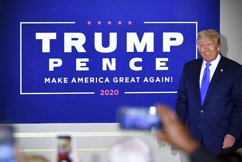 """President Trump stands beside a sign that reads, """"Trump Pence Make America great again 2020."""""""