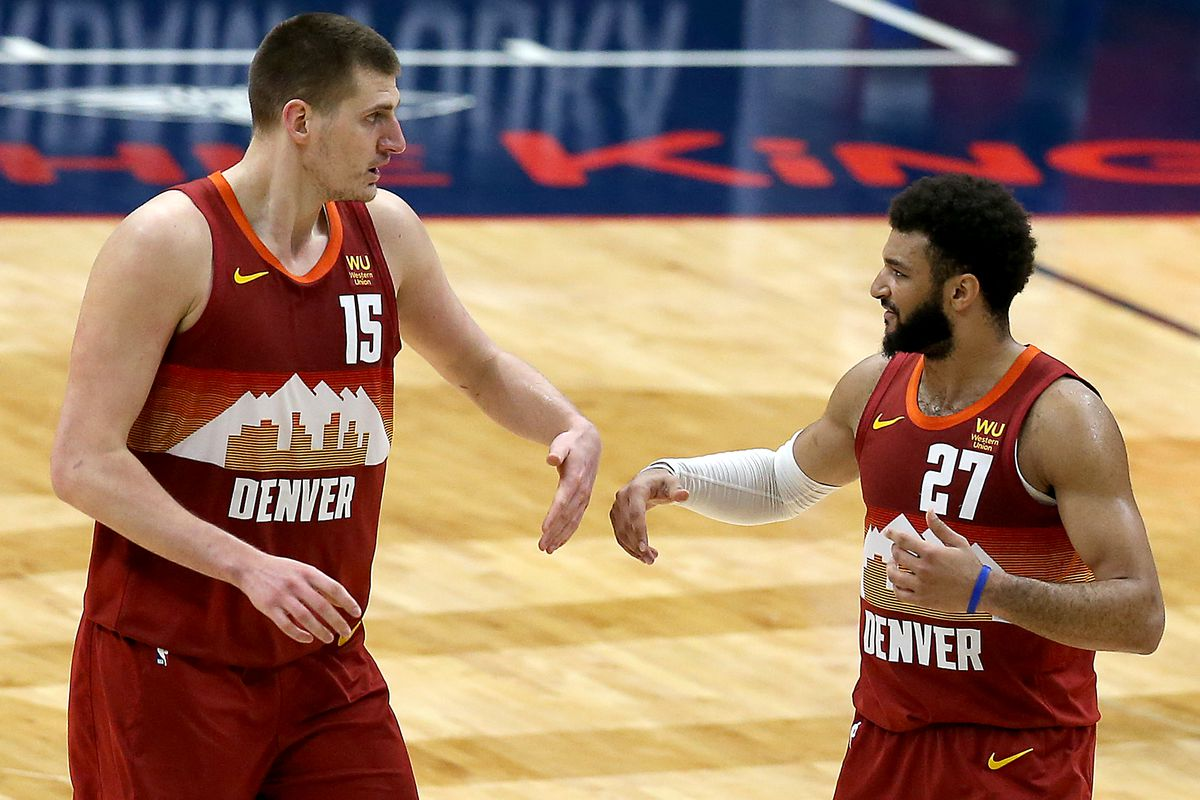 Nikola Jokic of the Denver Nuggets and Jamal Murray of the Denver Nuggets react after scoring during the third quarter of an NBA game against the New Orleans Pelicans at Smoothie King Center on March 26, 2021 in New Orleans, Louisiana.