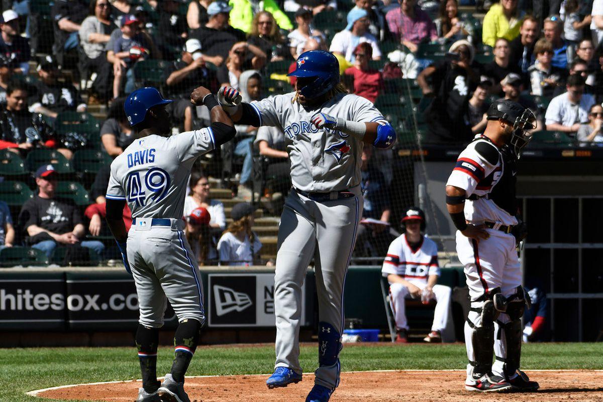 Vladimir Guerrero Jr. jumps and high-fives a teammate