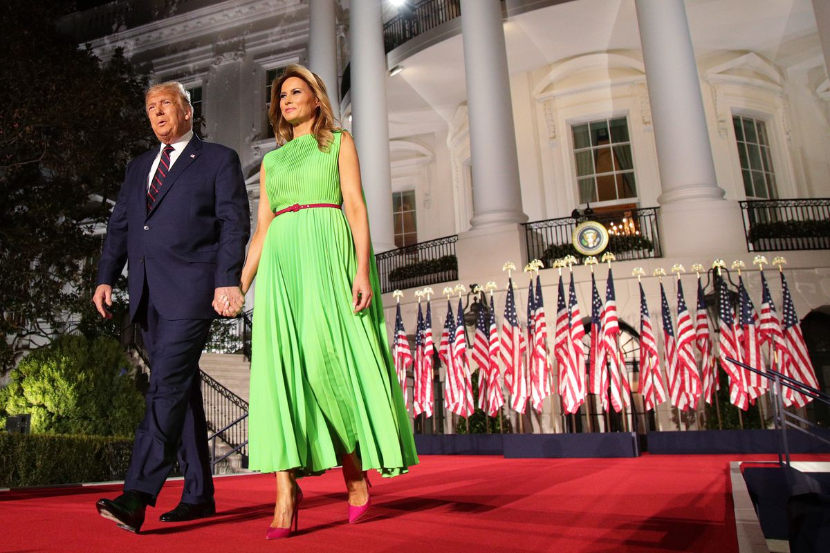 Donald Trump and Melania Trump standing next to one another on stage outside the White House.
