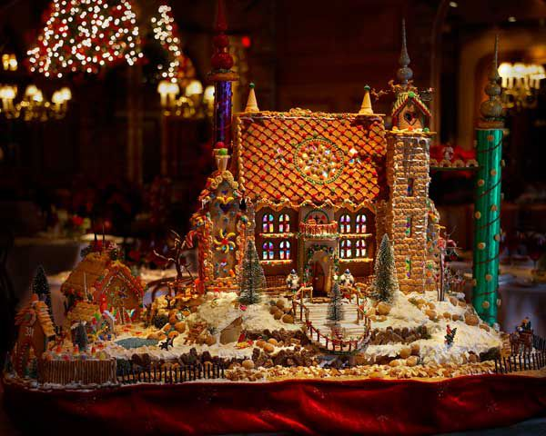 Decorative gingerbread house idea with detailed windows, gingerbread roof, and surrounding scenery featuring Christmas trees and snow.