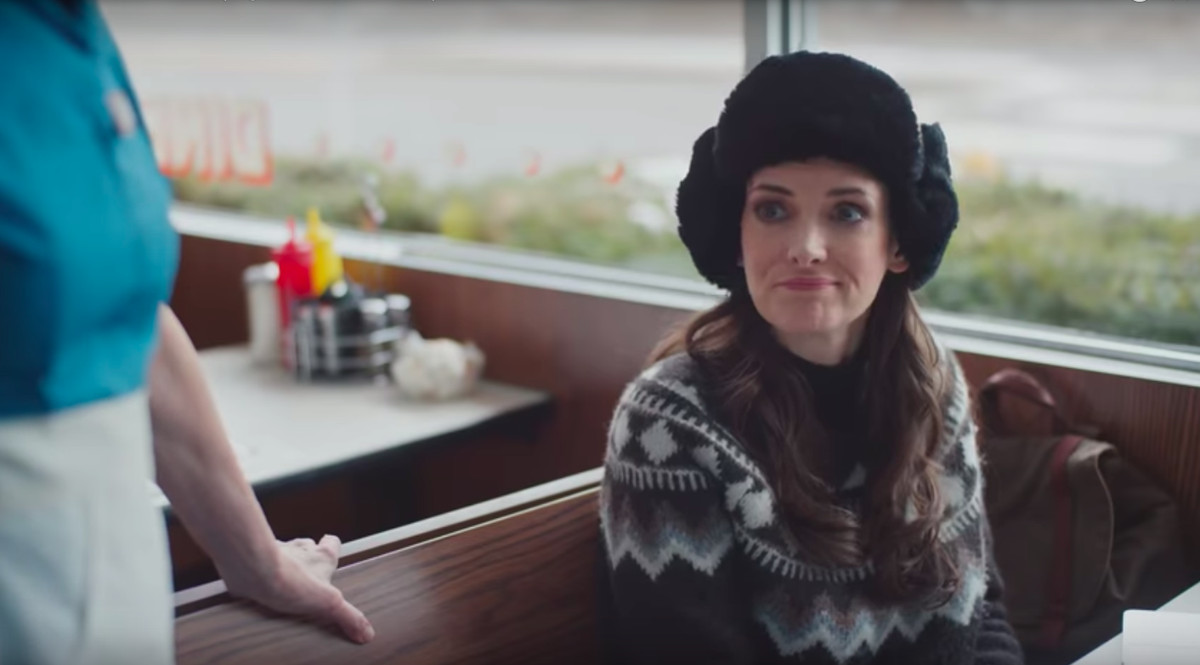 Winona Ryder in Mickey's by Willy wearing a pattered ski sweater and a fuzzy black earflap hat. She's making a half smile face while talking to a waitress.