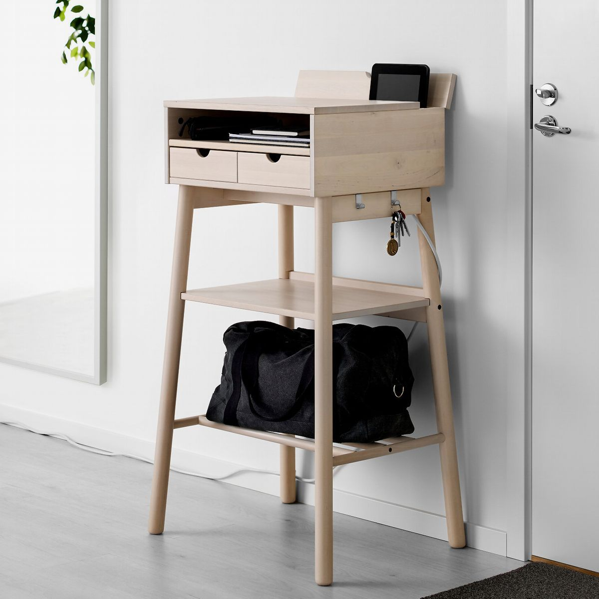 Light wood standing desk with two shelves underneath.