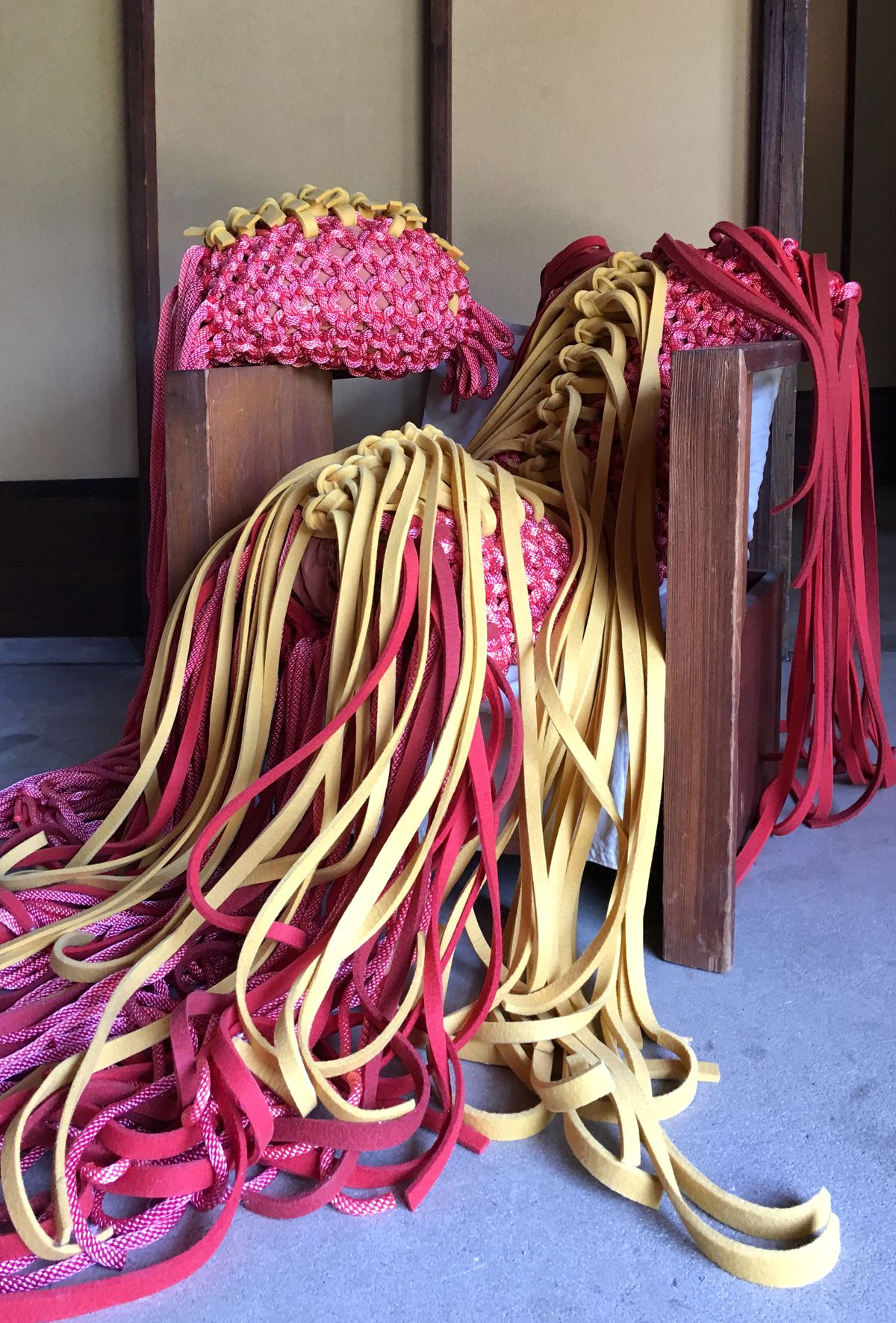A detail of an exhibition shows intricate knots and long strips of soft red and yellow felt and slick nylon rope woven into intricate knots.