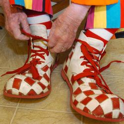 """In this March 29, 2012, photo, Floyd """"Creeky"""" Creekmore ties his oversized shoes while getting dressed before a visit with children at a circus in Billings, Mont. Guinness World Records has anointed the world's oldest performing clown, and it's none other than Creekmore, a former Montana rancher who's been donning the big nose and bright makeup for almost eight decades."""