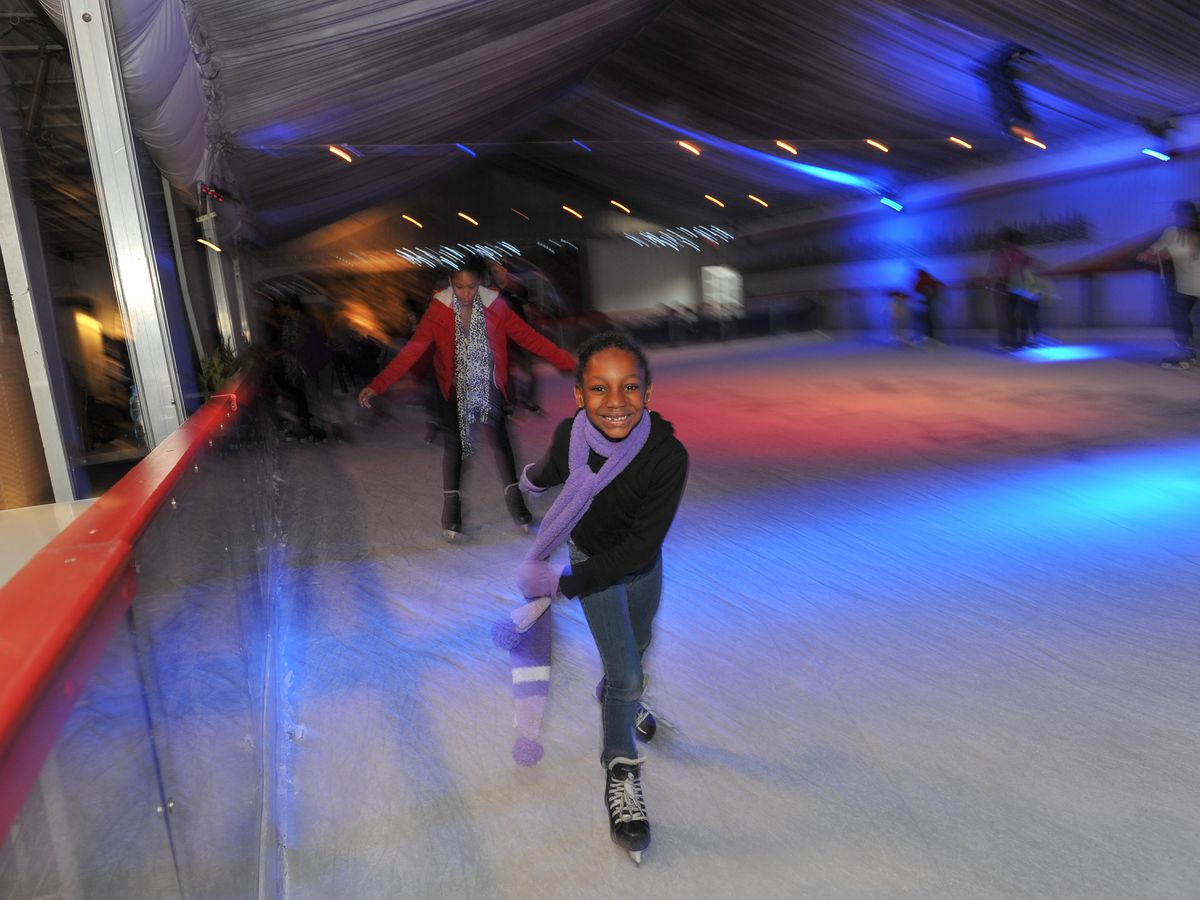 Girl ice skating on rink in a tent.
