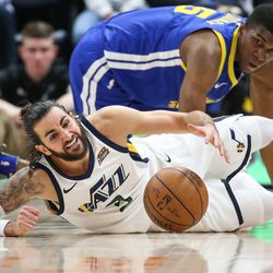 Utah Jazz guard Ricky Rubio (3) dives for a loose ball ahead of Golden State Warriors forward Kevon Looney (5) during the game at Vivint Arena in Salt Lake City on Tuesday, April 10, 2018.