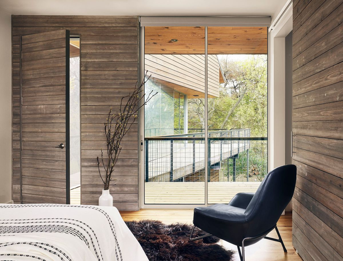 Timber-clad bedroom with a view of a deck and trees.