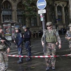 Police officers and soldiers seal off the access to Notre Dame cathedral after a man attacked officers with a hammer while patrolling the esplanade in front of the famous landmark, in Paris, France, Tuesday, June 6, 2017. Paris prosecutors have opened a counterterrorism investigation after an unidentified assailant attacked police with a hammer outside Notre Dame Cathedral.