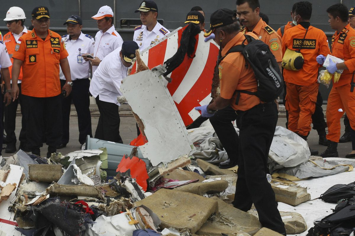 A rescuer inspects a part of Lion Air plane flight JT 610 retrieved from the waters where it's believed to have crashed at Tanjung Priok Port in Jakarta, Indonesia, Tuesday, Oct. 30, 2018. Relatives have provided samples for DNA tests to help identify vic