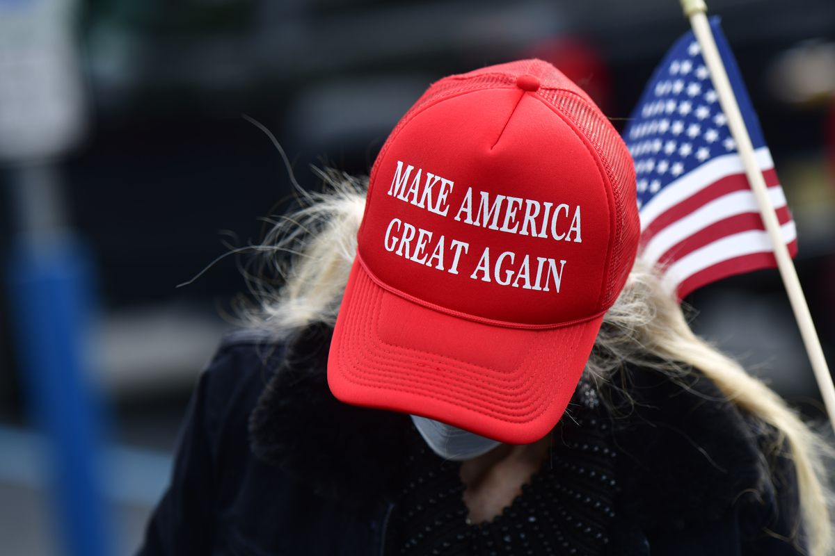 """A blond woman in a face mask wears a red """"Make America Great Again"""" hat, with a small US flag behind her."""