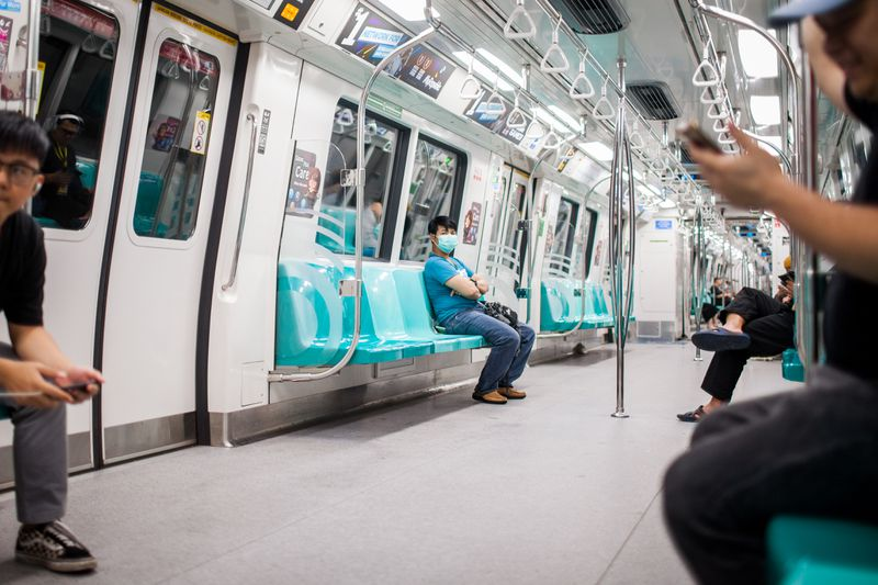 Residents, many in masks, sit several seats apart on a brightly lit train.