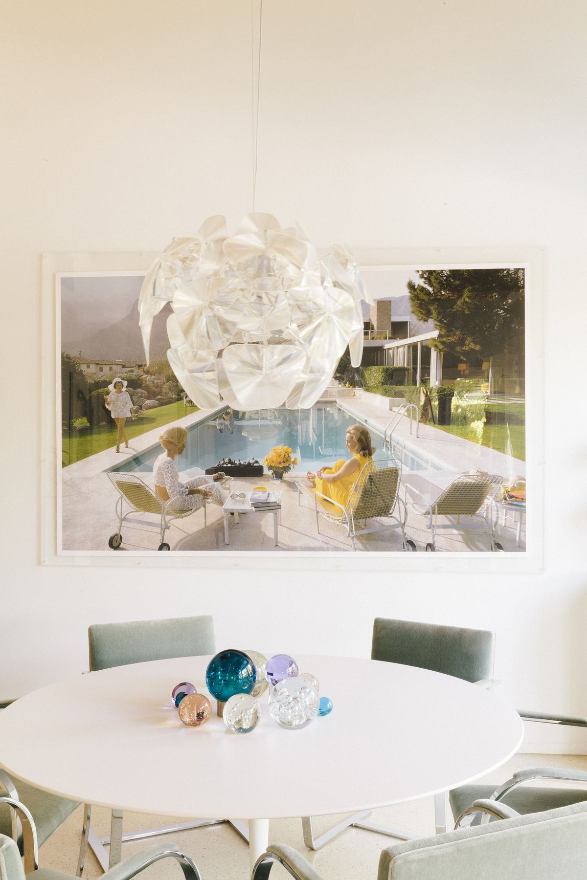 There is a round white table with several chairs. On the table are various assorted colorful glass baubles. Above the table on the white wall is a colorful art print. There is a hanging white light fixture.