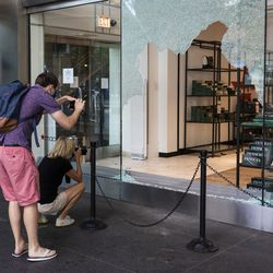 People take photos of Macy's at 835 N. Michigan Ave. in the Water Tower Place on the Magnificent Mile after looting broke out overnight in the Loop and surrounding neighborhoods, Monday morning, Aug. 10, 2020.