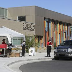 Kitchen manager Yedris Alzola-Rodriguez asks a driver how many meals they need outside of Edison Elementary School in Salt Lake City on Monday, Sept. 28, 2020. Nutrition technicians and kitchen managers typically hand out between 300 to 400 lunches a day at Edison. Meal service hours have extended and will now go from 10:30 a.m. to 12:30 p.m.