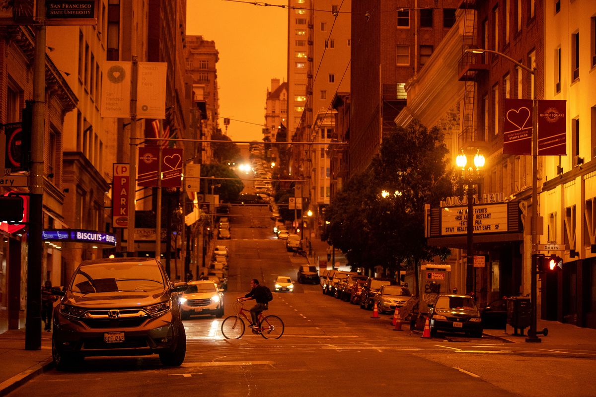 Orange sky descended upon San Francisco as wildfires burned in California. There is a picture of a city street with buildings on either side and an orange hue everywhere.