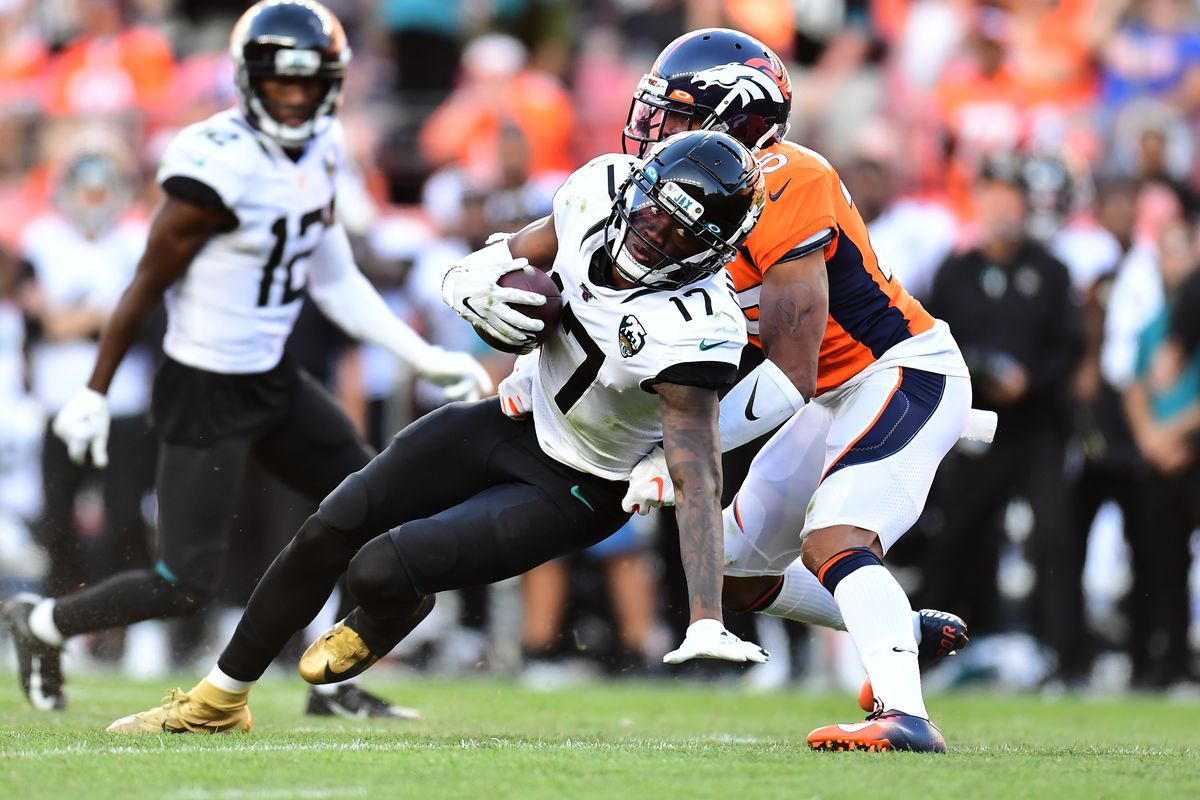 Jacksonville Jaguars wide receiver D.J. Chark pulls in a reception past Denver Broncos cornerback Chris Harris in the fourth quarter at Empower Field at Mile High.