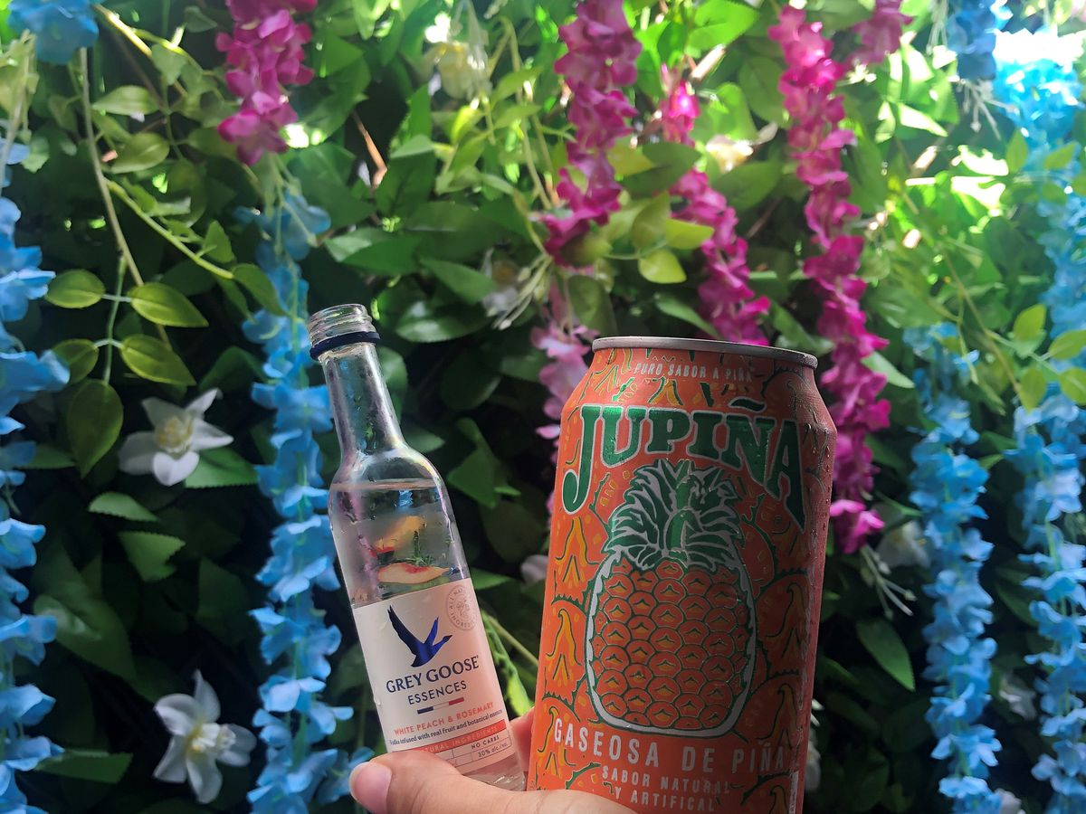 A hand holds a small bottle of Grey Goose Essences and a pineapple soda in front of a wall of flowers