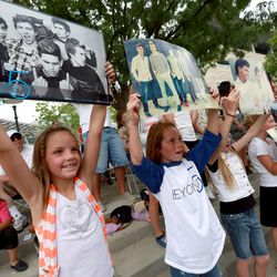Bryton Harmon, left, and Mia Ward hold up posters of Beyond 5 as the band performs at Five-O Fest, a free community festival hosted by the Utah Anti-Bullying Coalition, Safe2Help and the Salt Lake City Police Foundation outside of the Public Safety Building in Salt Lake City on Saturday, May 31, 2014.