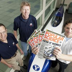 Dr. Perry Carter, Kelly Hales and Trey Mortensen pose with copies of Popular Science that features BYU's streamliner.