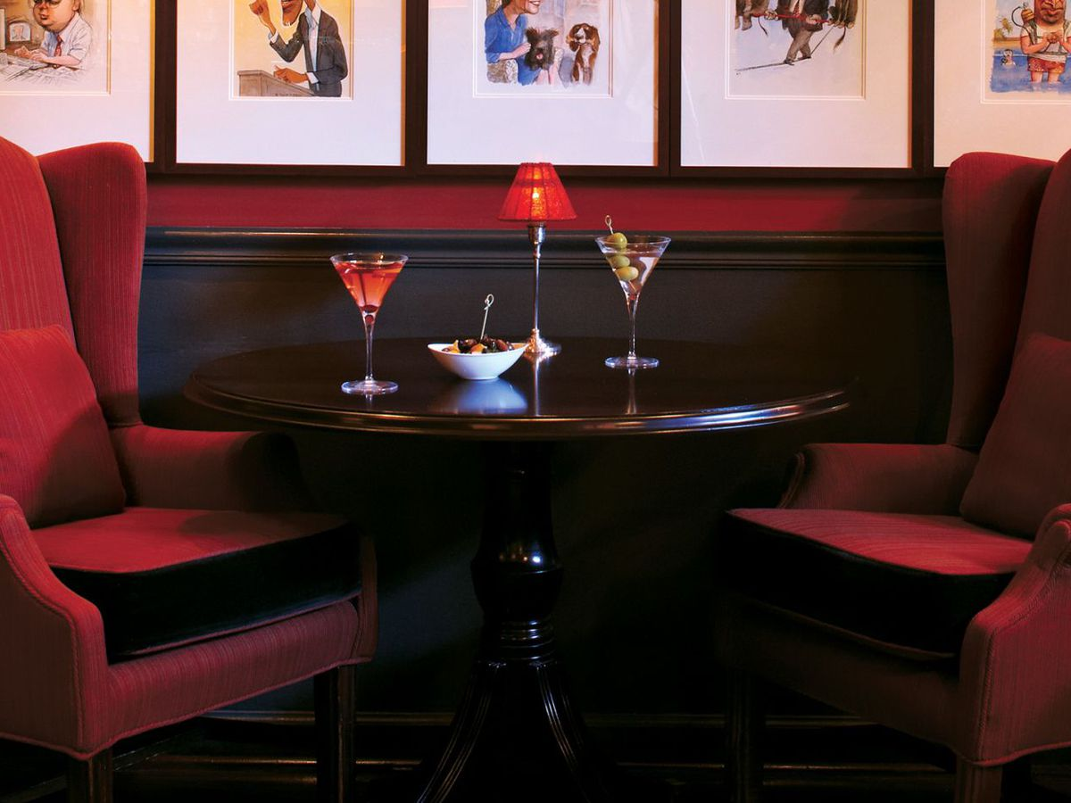 Two red chairs, a table, and two cocktails on the table, including a martini with olives to the right