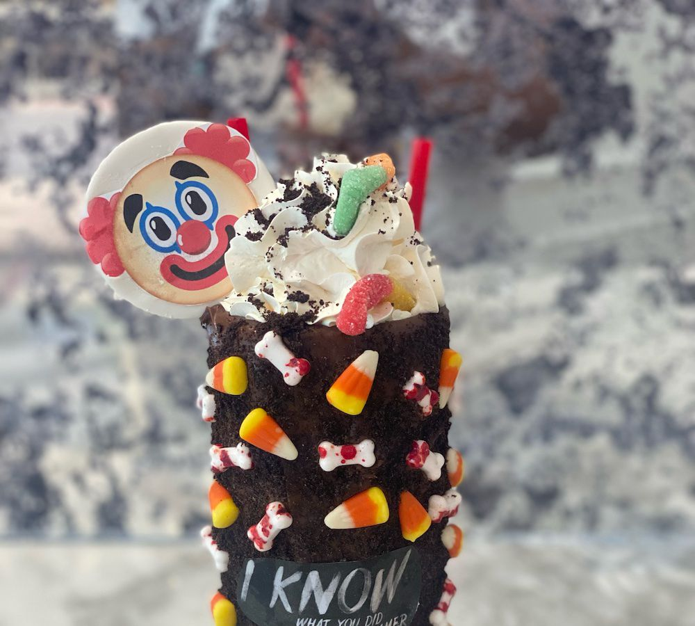 A milkshake with candy corn on the cup and a clown on top