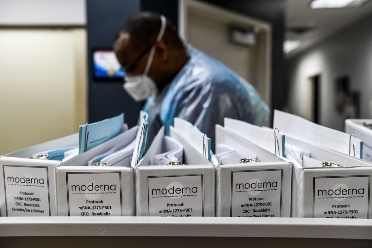 A man in protective gear and a mask seen in the background with Moderna files in the foreground.
