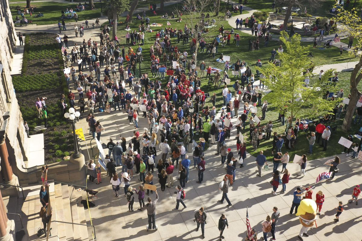 """Members of the group """"Freedom in the Numbers! No More Social Distance!"""" rally against a state stay-at-home request at the Salt Lake City-County Building in Salt Lake City on Saturday, April 18, 2020."""