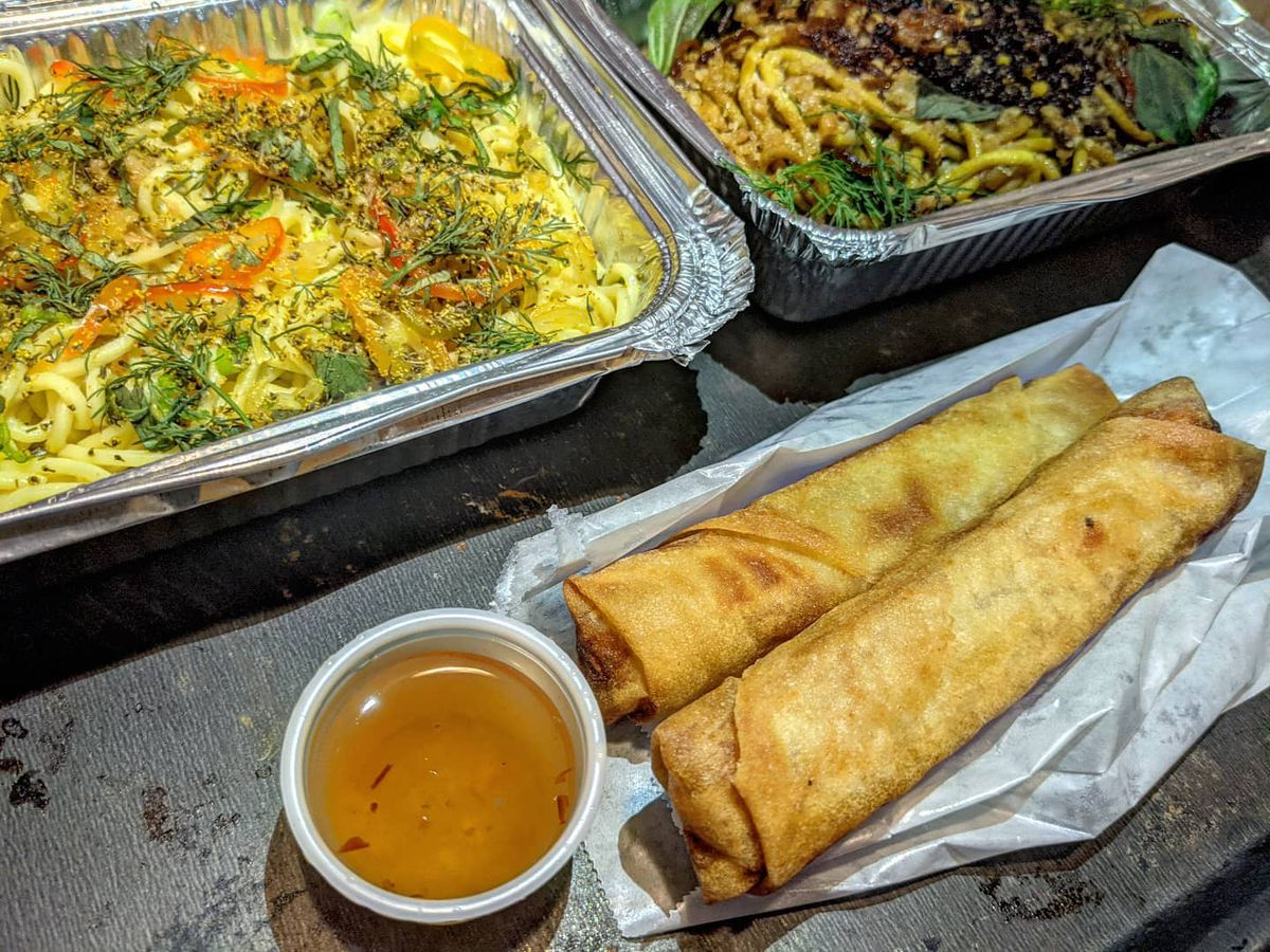 Two aluminum takeout containers are full of noodles, and two thick eggrolls sit in front, with a small plastic cup of dipping sauce