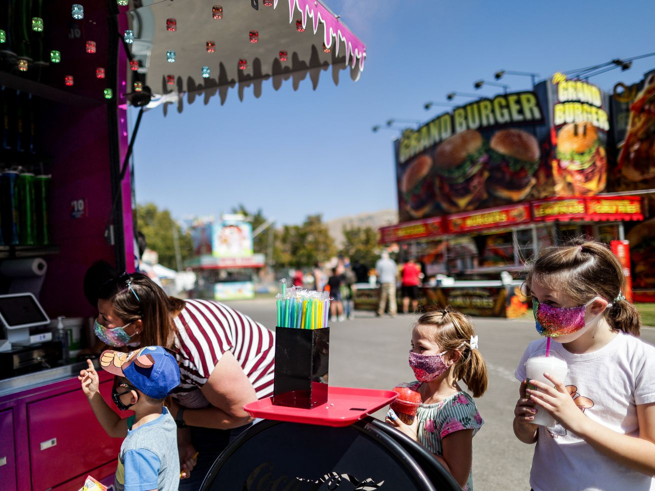Emmy Doney, right, puts her straw under her mask as she gets slushies with her mother, Cassie, and brother Ryder, 4, left, and sister Brielle, 5, at the Utah State Fair at the fairpark in Salt Lake City on Friday, Sept. 11, 2020.