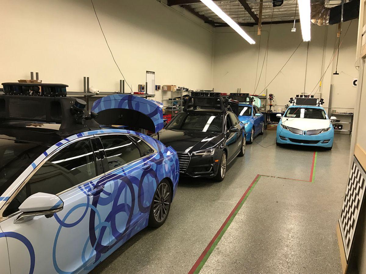 Autonomous cars parked in Drive.ai's garage include a Lincoln sedan and an Audi sedan.