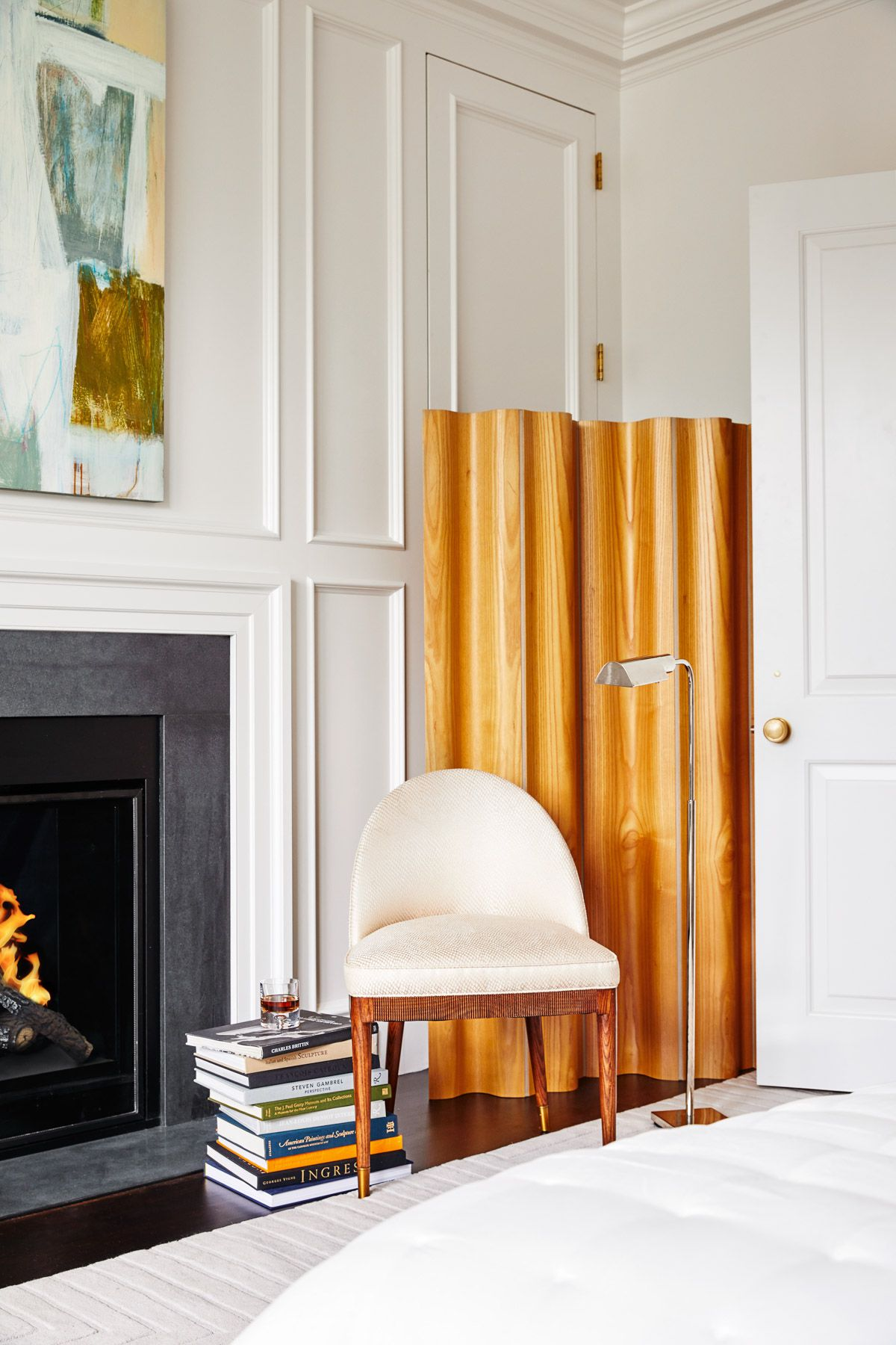 A modern white chair with wooden legs sits in front of a golden-wood room divider and fireplace. On the floor is a stack of large art and design books.