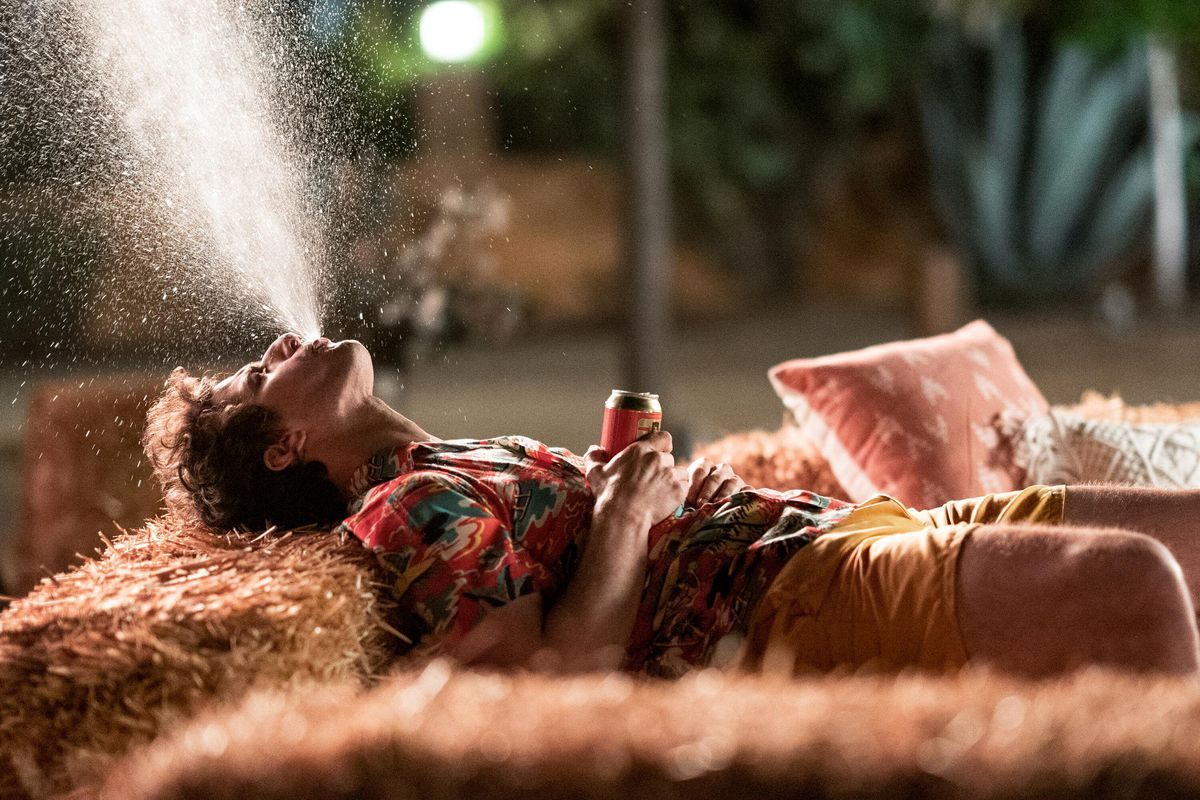 Andy Samburg spits a spray of beer into the air while lying on his back in Palm Springs.